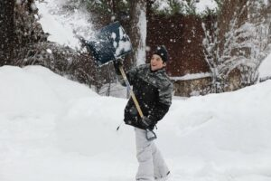 Teenage boy shovels snow with a smile