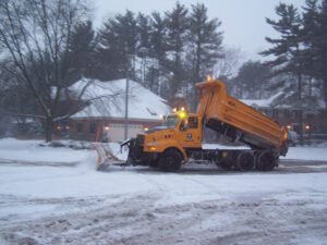 Snow plow clearing snow covered residential street
