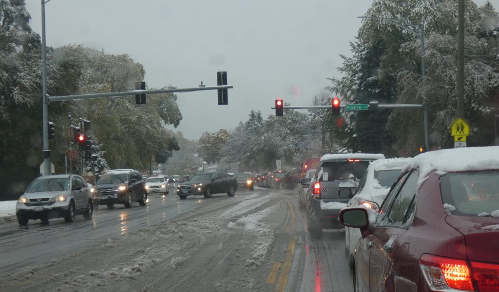 Cars waiting at red light in a wet, snowy street